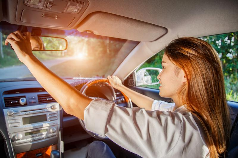 Young asian woman driver adjusting her rearview mirror in the car royalty free stock photography