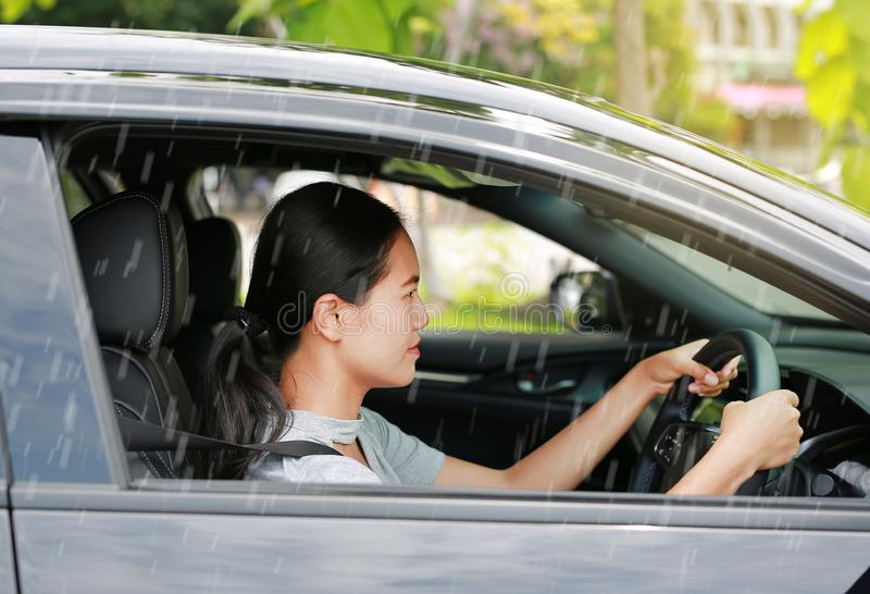 Young Asian woman driving a car while raining royalty free stock images