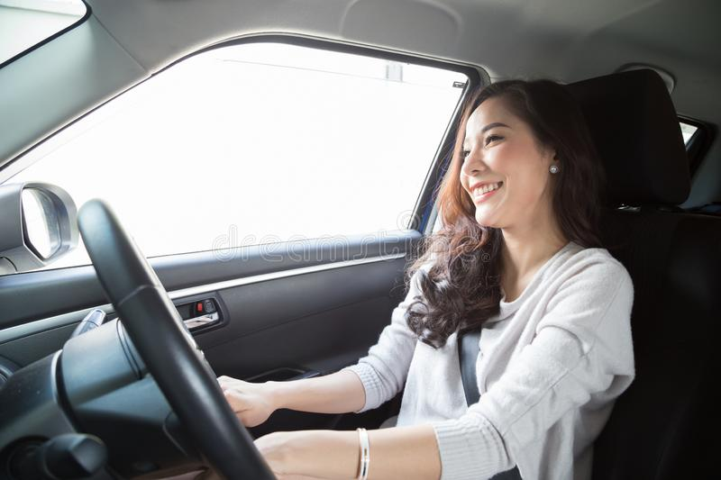 Young Asian woman driving a car and smile happily with glad positive expression during the drive to travel journey. royalty free stock photo