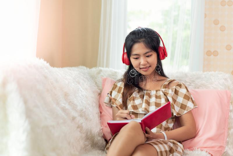 Young Asian woman enjoy listening to music with headphones and reading a book , happy and relaxing time stock photo