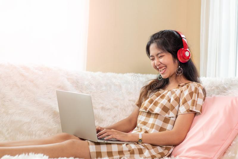 Young Asian woman enjoy listening to music with headphones and using laptop, happy and relaxing time royalty free stock photos