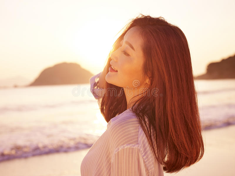 Young asian woman enjoying morning sunlight. Young asian woman enjoying the early morning sunlight on beach royalty free stock photos