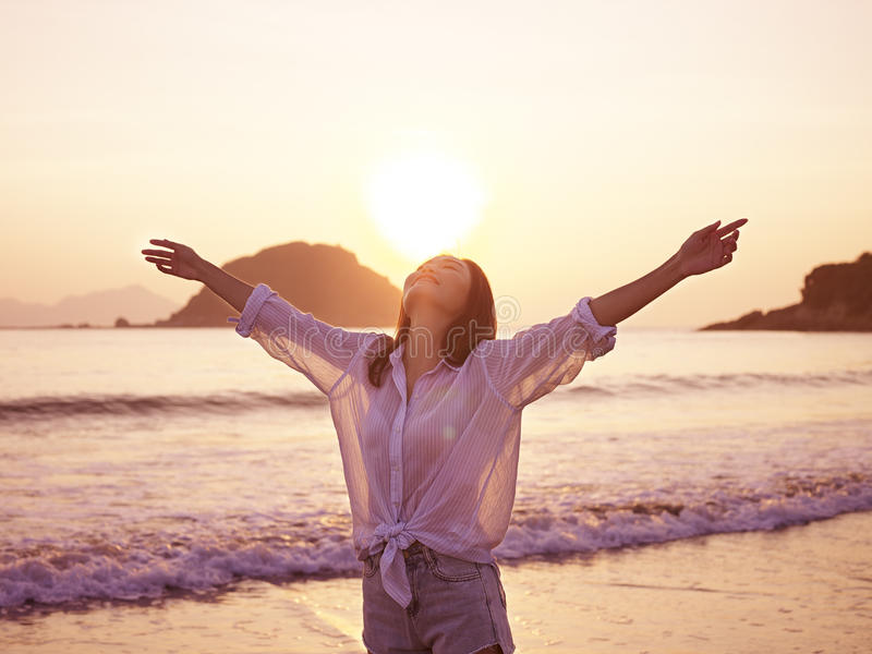Young asian woman enjoying morning sunlight. Young asian woman enjoying the early morning sunlight with open arms on beach royalty free stock image