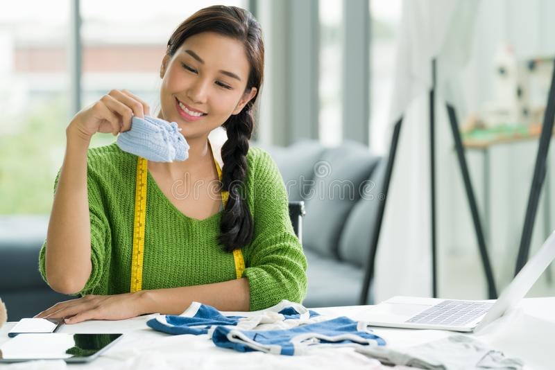 Young Asian woman entrepreneur / fashion designer for baby clothes working in studio royalty free stock photo