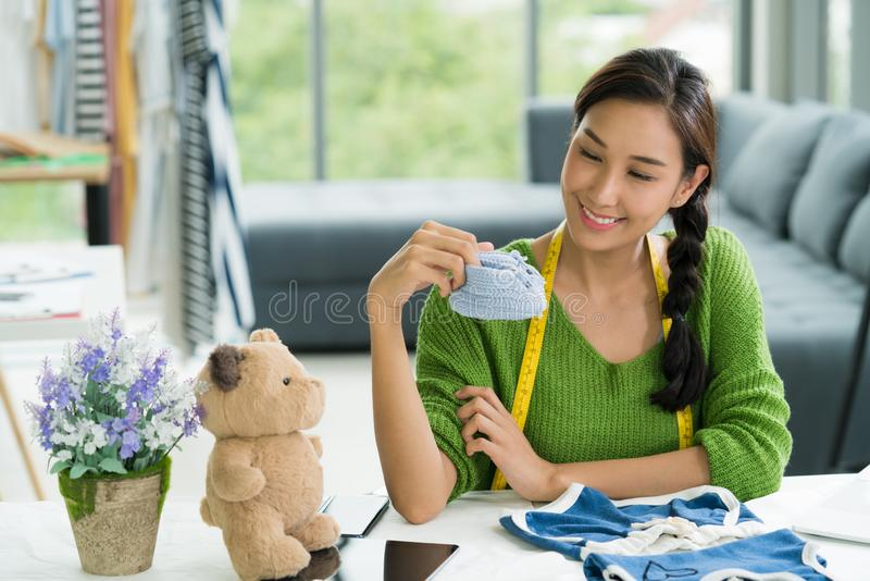 Young Asian woman entrepreneur / fashion designer for baby clothes working in studio royalty free stock photos