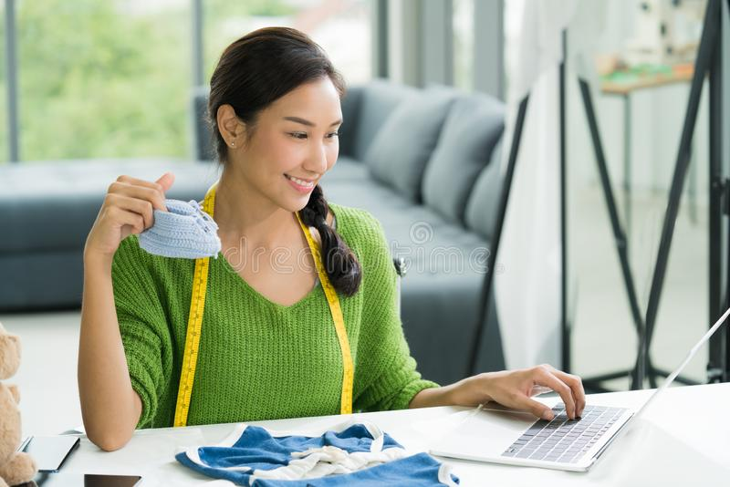 Young Asian woman entrepreneur / fashion designer for baby clothes working in studio royalty free stock images