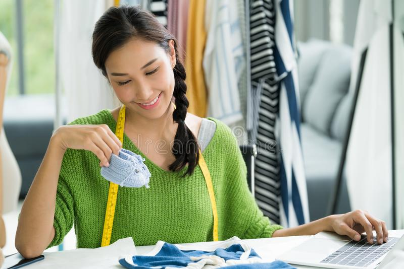 Young Asian woman entrepreneur / fashion designer for baby clothes working in studio royalty free stock photography