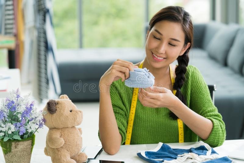 Young Asian woman entrepreneur / fashion designer for baby clothes working in studio stock photos