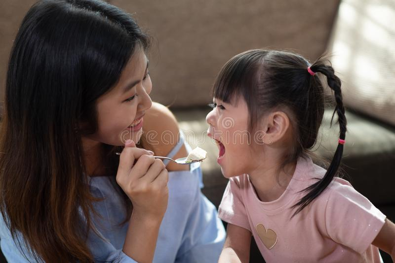 Young Asian woman feeding her younger sister with spoon of tasty cake. Portrait of happy Asian women feeding her younger sister with spoon of tasty cake stock photos
