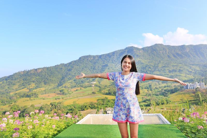 Young Asian woman feeling free with arms wide open at beautiful trees and mountains on blue sky with white puffy cloud.  royalty free stock images