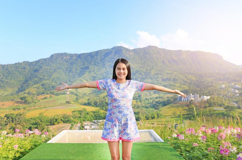 Young Asian woman feeling free with arms wide open at beautiful trees and mountains on blue sky with white puffy cloud.  royalty free stock photos