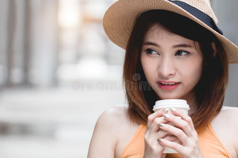 Young Asian woman feeling happy holding coffee cup royalty free stock photography