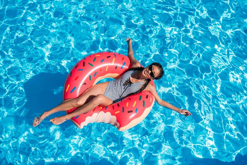 Young asian woman floating on inflatable donut royalty free stock image
