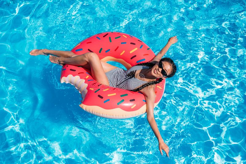 Young asian woman floating on inflatable donut stock photo