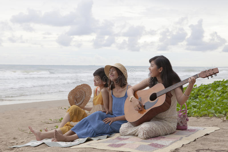Young asian woman friend playing guitar on sea beach happiness e stock photo