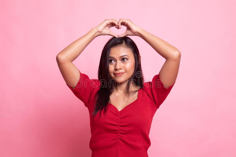 Young Asian woman gesturing  heart hand sign. Young Asian woman gesturing heart hand sign on pink background stock photography