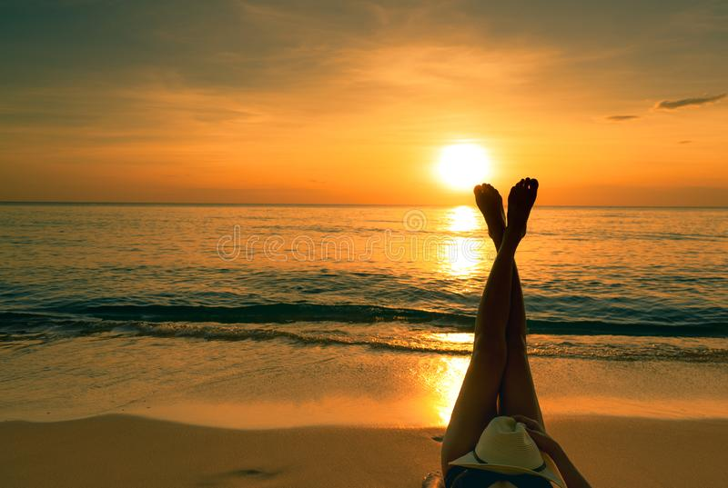 Young Asian woman with hat relaxing on the beach at sunset. Girl lying on sand beach. Upside woman bare feet at seaside. Holiday. Travel alone. Summer vibes royalty free stock photography