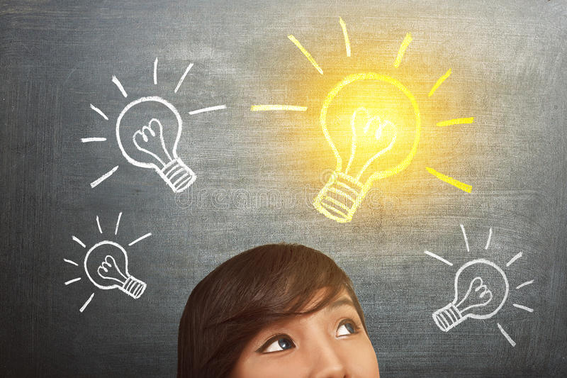 Young asian woman have idea with bright light bulb over head royalty free stock photo