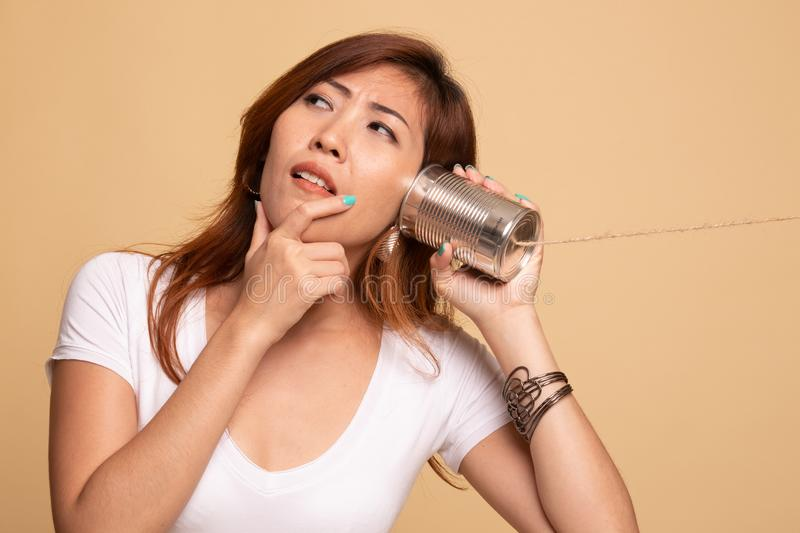Young Asian woman hearing with tin can phone and thinking. On beige background royalty free stock images