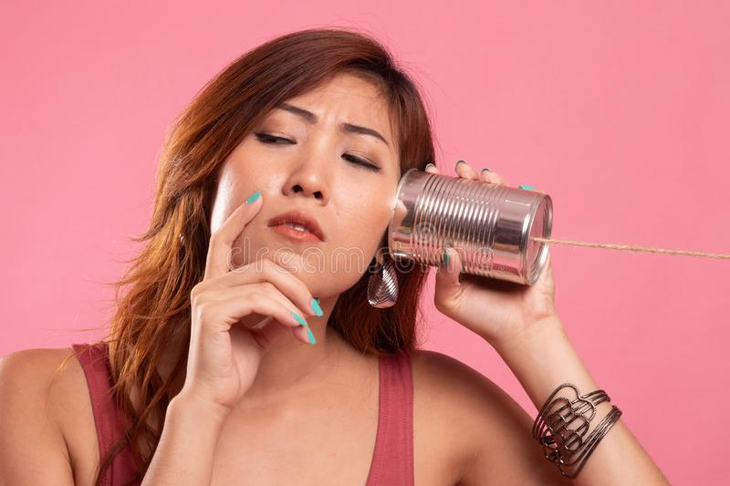 Young Asian woman hearing with tin can phone and thinking. On pink background stock photo