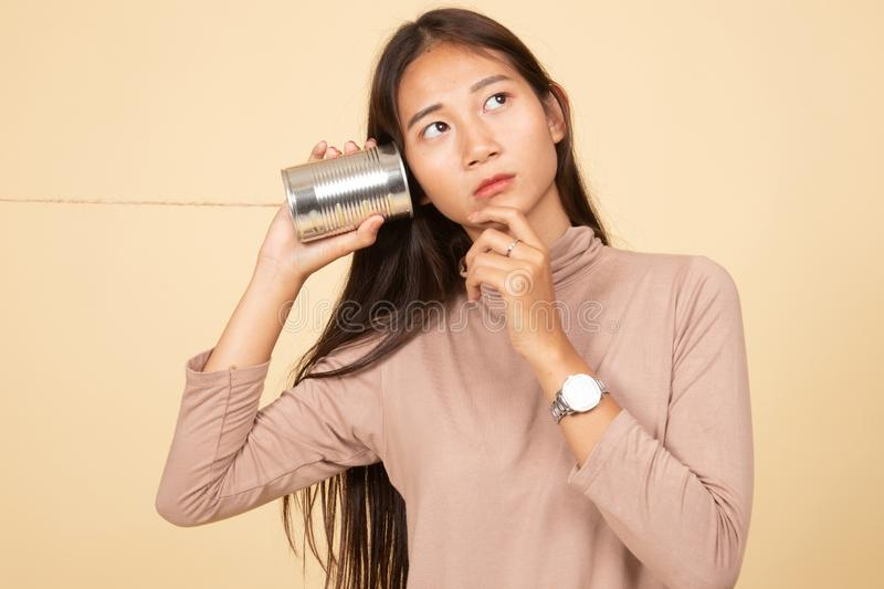 Young Asian woman hearing with tin can phone and thinking. On beige background stock photography