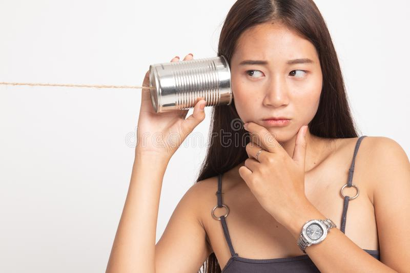 Young Asian woman hearing with tin can phone and thinking. On white background stock photo