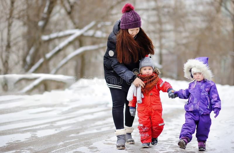 Young asian woman helping caucasian toddler boy anf girl with their winter clothes stock photography