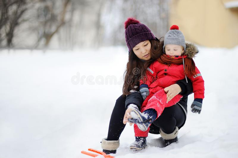 Young asian woman helping caucasian toddler boy with his winter clothing stock photo