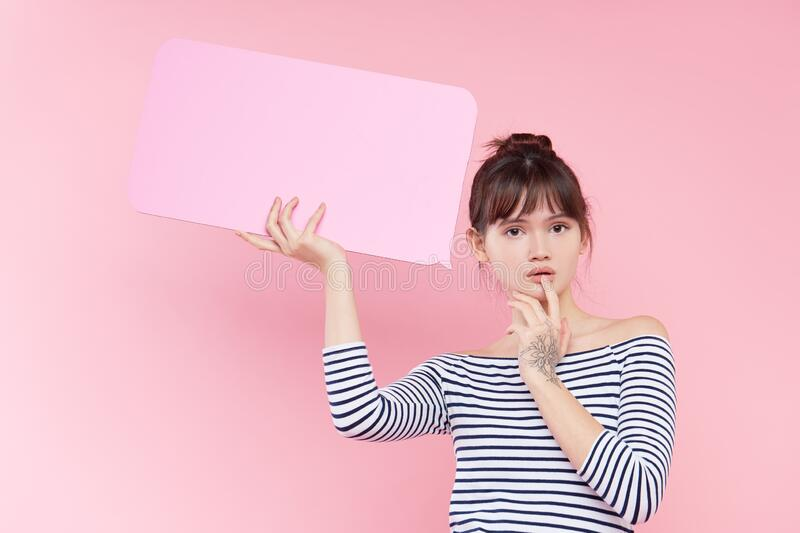 Young Asian woman holding a blank banner plate in her hands with place for text. Fake news concept. Pink background royalty free stock photography