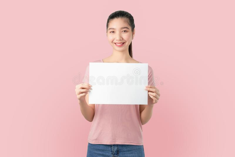 Young Asian woman holding blank paper with smiling face and looking on the blue background. for advertising signs. stock images