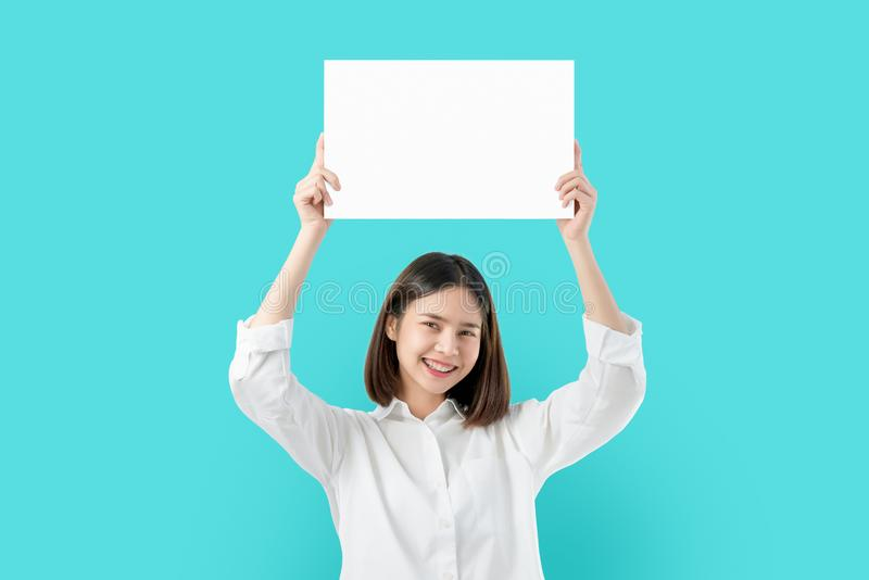 Young Asian woman holding blank paper with smiling face and looking on the blue background. for advertising signs. royalty free stock image