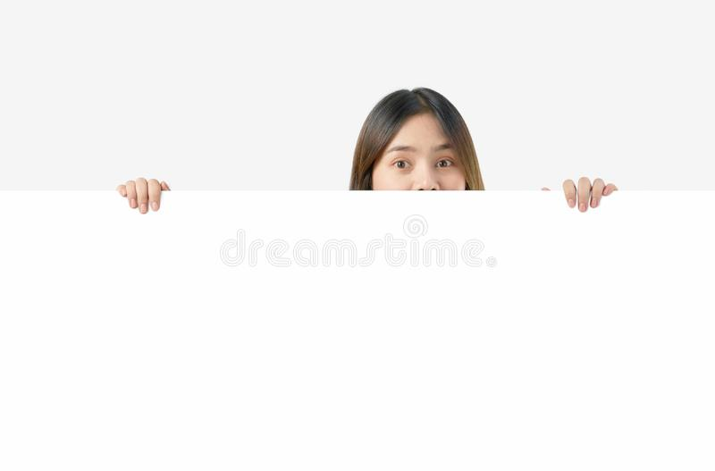 Young Asian woman holding blank paper with smiling face and looking on the blue background. for advertising signs. stock photography