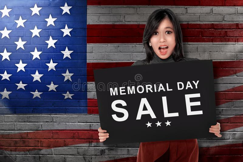 Young asian woman holding board with text memorial day sale royalty free stock photos