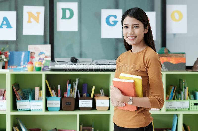 Young asian woman holding books standing at library background, stock photos