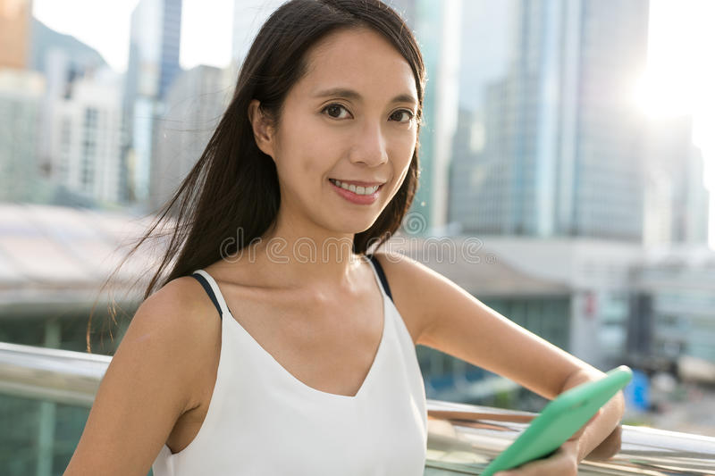 Young asian woman holding cellphone in the city. Asian young woman royalty free stock image