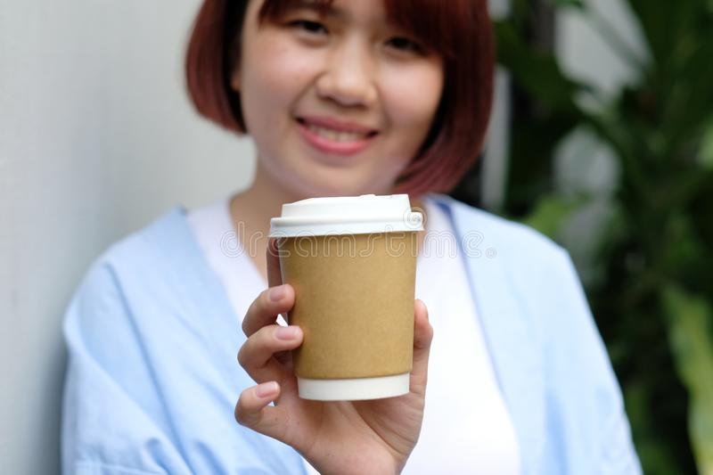 Young asian woman holding a coffee cup with smilling face, hot drink royalty free stock image