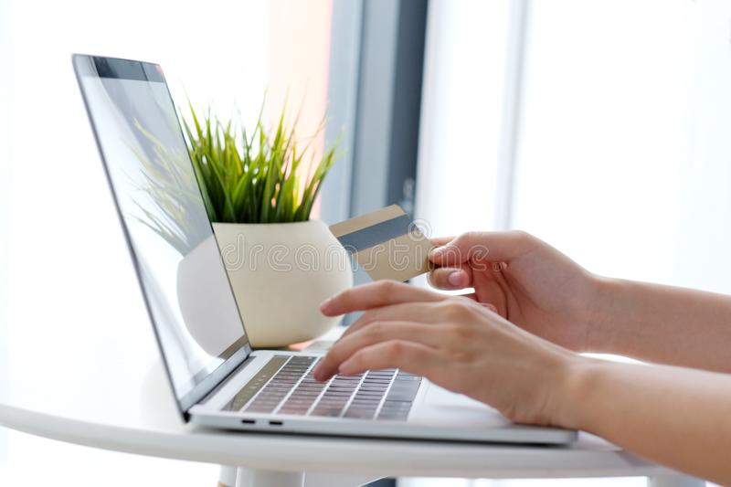 Young asian woman holding credit card and using laptop computer. For shopping on line at cafe, business and technology concept, digital marketing, casual royalty free stock image