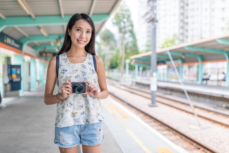 Young asian Woman holding digital camera in light rail station stock images