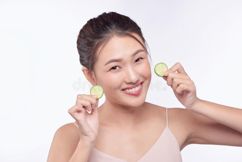 Young asian woman holding and eating cucumber slice in her hands isolated on white background.  royalty free stock photo