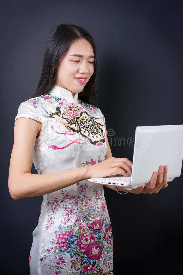Young asian woman holding a laptop device. Young asian woman holding a laptop wearing chinese dress stock images