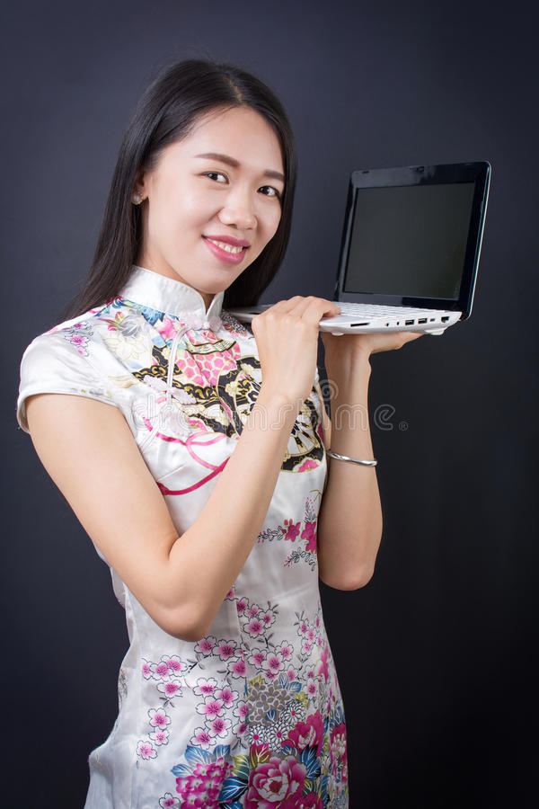 Young asian woman holding a laptop device. Young asian woman holding a laptop wearing chinese dress stock photo