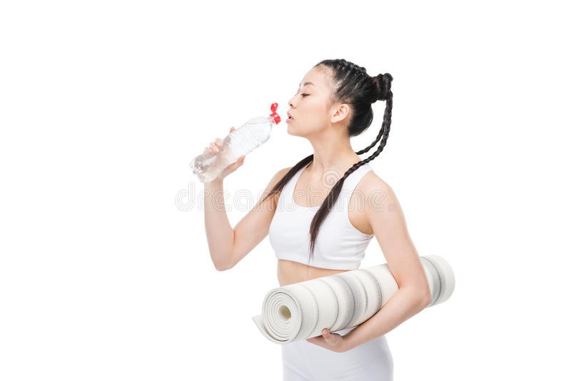 Young asian woman holding yoga mat and drinking water from bottle stock image