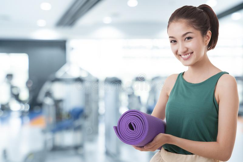 Young asian woman holding a yoga mat with fitness sport training club background stock photo