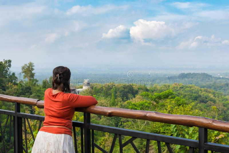 Young Asian woman leaning on railing at scenic lookout stock photos
