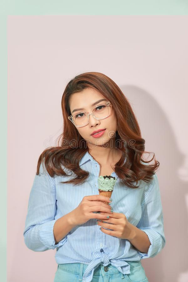 Young asian woman on light pink background. Stylish young woman with ice cream isolated royalty free stock photos