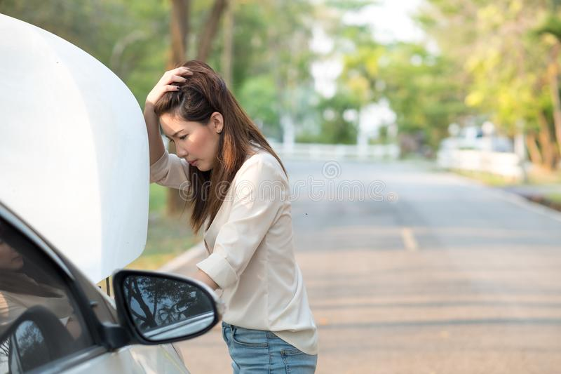 Young Asian woman looking at her broken down car royalty free stock photos