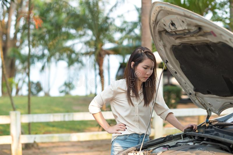 Young Asian woman looking at her broken down car royalty free stock photography