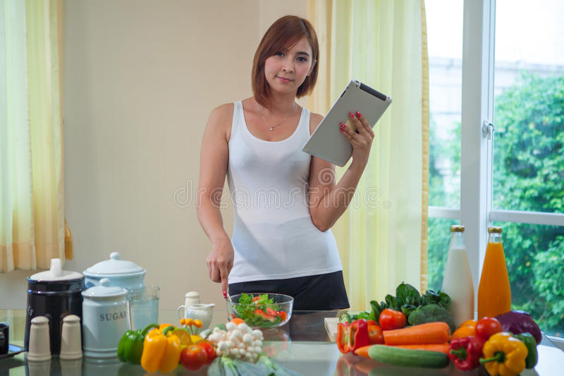 Young asian woman looking for a recipe on the internet stock photography