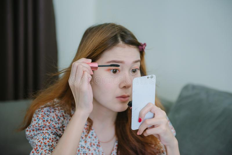 Young asian woman looks into pocket mirror applying make-up after taking a shower at home. royalty free stock photo