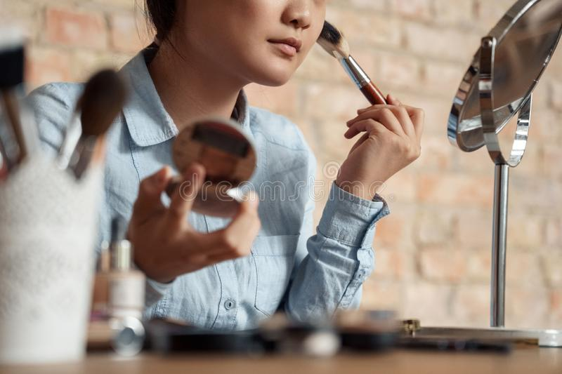 Freestyle. Asian girl makeup artist sitting looking at mirror applying rouge close-up royalty free stock photos